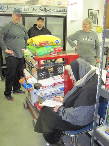 Staff and volunteers of the food bank weigh the final 381 pounds of pet food collected by the 2015 pet food drive.